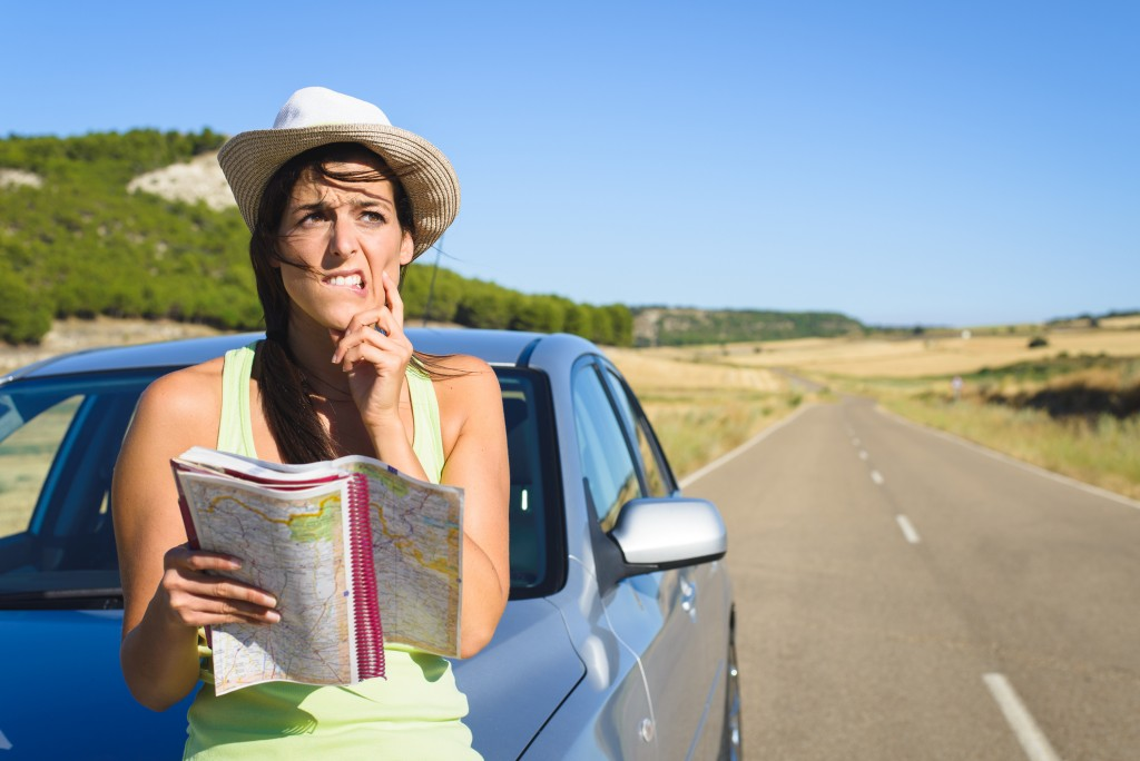 Confused lost woman on car roadtrip travel problem searching in road map.